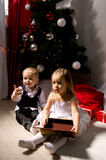 Children unpack gifts. Under the Christmas tree New Year's Eve Royalty Free Stock Photos