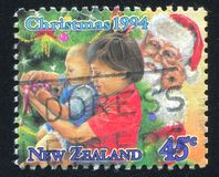 Children Unpacking Presents under Christmas Tree. NEW ZEALAND - CIRCA 1994: stamp printed by New Zealand, shows Children Unpacking Presents under Christmas Tree stock photography