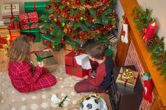 Children unwrapping Christmas presents. Overhead photo of children, a boy and a girl, sitting by the tree unwrapping their presents on Christmas day Stock Image