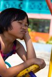 Children upset frown. Girl sitting on an upset scowl driving school playground in one of Thailand Royalty Free Stock Image
