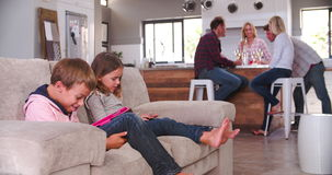 Children Use Digital Devices As Parents Drink Wine stock footage