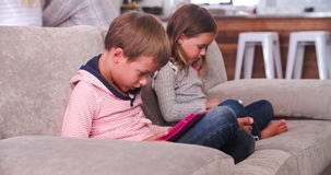 Children Use Digital Devices As Parents Talk In Background stock video footage