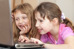 Children using computer. Two happy little girls using laptop royalty free stock image