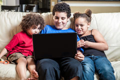 Children using computer. Grop of three kids at home looking at laptop computer Stock Photography