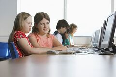 Children (10-12) using computer in computer lab