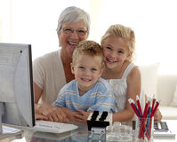 Children using a computer with their grandmother. Happy children using a computer with their grandmother at home Stock Photo
