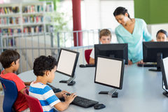 Children using computers as teacher teaching them. In classroom Royalty Free Stock Photo