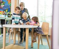 Children Using Digital Tablet In Library Royalty Free Stock Image