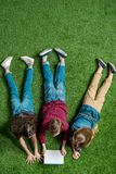 Children using digital tablet while lying on grass Stock Photos