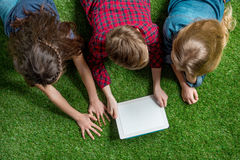 Children using digital tablet while lying on grass Stock Images