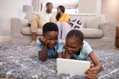 Children using digital tablet while parents siting on sofa at home Stock Images