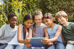 Children using digital tablet at park Stock Photo