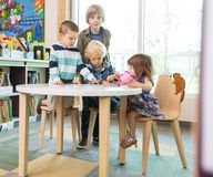 Children Using Digital Tablet At Table In Library Royalty Free Stock Images