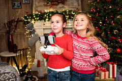 Children using hexacopter drone. Happy children standing near fireplace and using hexacopter drone stock photo