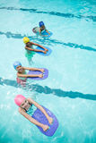 Children using kickboard while swimming in pool Stock Photography