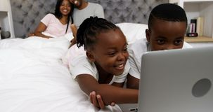 Children using laptop while couple smiling in background 4k. Children using laptop while couple smiling in background at home 4k stock video footage
