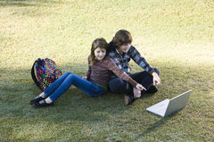 Children using laptop in park Stock Images