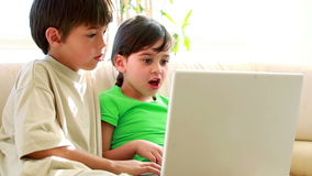 Children using a laptop together. In the living room stock video