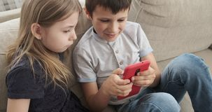 Children using mobile phone on sofa. Boy and girl using mobile phone on sofa at home stock footage