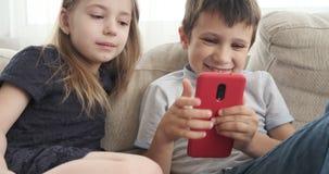 Children using mobile phone on sofa stock video