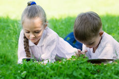 Children using PC and smartphone laying Stock Photos