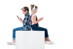 Children using smartphones in headphones while sitting on cube together. Isolated on white royalty free stock images