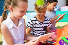 Children using tablet computer during birthday party Royalty Free Stock Image