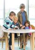 Children Using Tablet Computer At Desk In Library Stock Photo