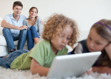 Children using a tablet computer with parents Stock Photos