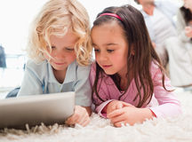 Children using a tablet computer while their parents are in the. Background in a living room stock photo