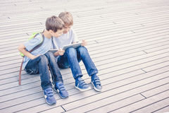 Children using tablet computers outdoor. People education learning technology leisure concept Stock Image