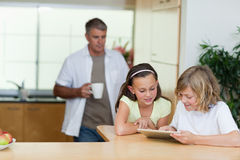 Children using tablet in the kitchen with father behind them Stock Photo