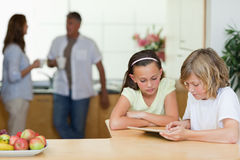 Children using tablet in the kitchen with parents behind them Stock Images