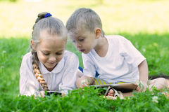Children using tablet PC and smartphone laying Stock Photography