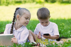 Children using tablet PC and smartphone in perk Royalty Free Stock Images