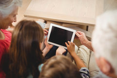 Children using tablet with their grandparents Stock Photo