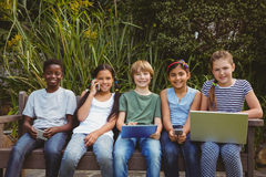 Children using technologies at park. Portrait of children using technologies at the park Royalty Free Stock Photo