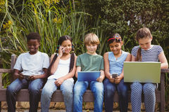 Children using technologies at park Stock Image
