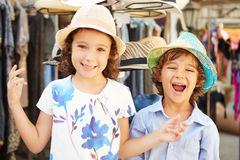 Children On Vacation Trying On Hats At Store Royalty Free Stock Photography