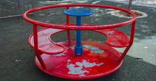 Children& vermelho x27; carrossel de s na jarda no verão imagem de stock