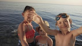 Cute children video chats on smart phone on beach