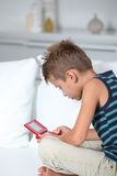 Children and video games. Little boy playing video games on sofa Royalty Free Stock Photography