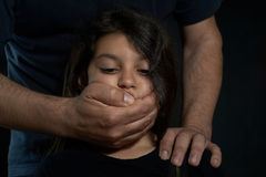 Children violence. Man's hands muzzle the mouth of a girl not to scream Royalty Free Stock Photos