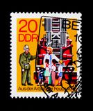 Children visit fire vehicle, From The Work Of The Fire Brigade serie, circa 1977. MOSCOW, RUSSIA - NOVEMBER 23, 2017: A stamp printed in Germany DDR shows stock photos