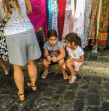 Children wait for shopping parents at street market in Paris, France Royalty Free Stock Photos