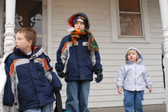 Children waiting. Three Children wait on a porch for the school bus in winter jackets and hats for their first day at a new school stock image