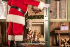 Children waiting for Santa Claus. Children sitting near fireplace and waiting for Santa Claus Royalty Free Stock Images