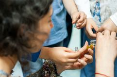 Children learning about plants and oils at a workshop. Children waiting for teacher to pour herbal oil in their little bottles Stock Image