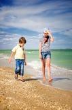 Children walk along the coast vertical stock image