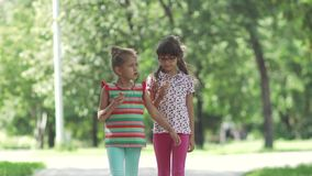 Children walk around the summer park and eat ice cream. Little girl smeared her face with ice cream. Carefree children eat ice cream in summer Park. two little stock footage